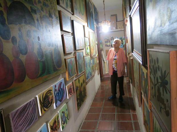 Elenir aprecia suas obras na parede de casa (Foto: Anna Gabriela Ribeiro/G1)
